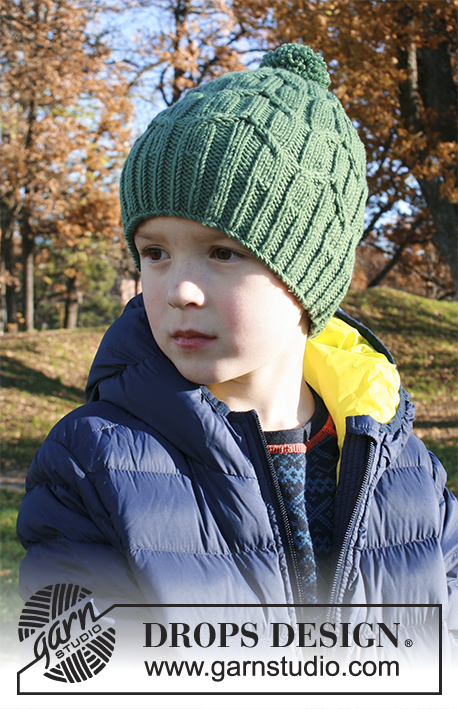 Green Bird / DROPS Extra 0-1358 - Knitted hat for children with cables and pompom in DROPS Merino Extra Fine. Size 2 - 9 years